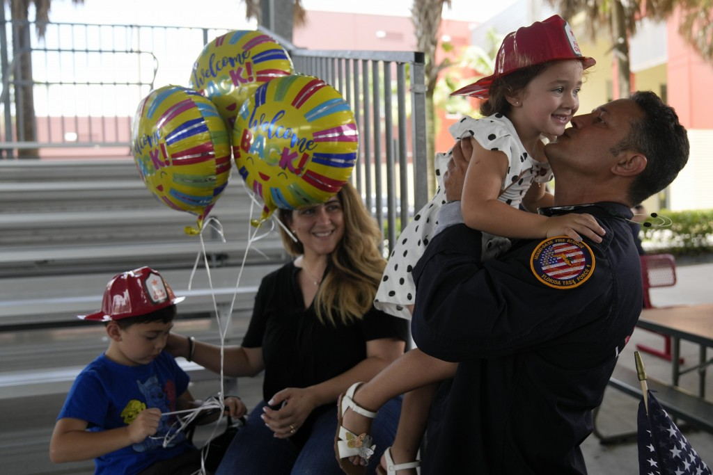 Capt. Eric Hernandez lifts up his daughter Isabella, 3, as his wife Yaimara and son Eric, 4, look on, as members of Miami-Dade Fire Rescue's urban sea...