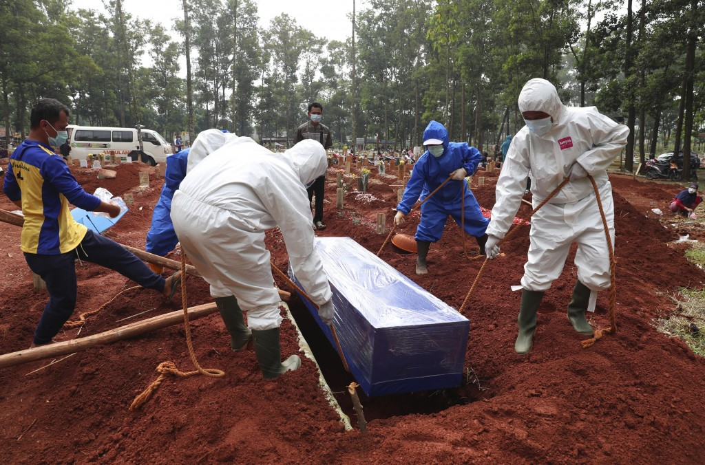 Workers in protective suits lower a coffin containing the body of a COVID-19 victim into a grave during a burial at Cipenjo cemetery in Bogor, West Ja...