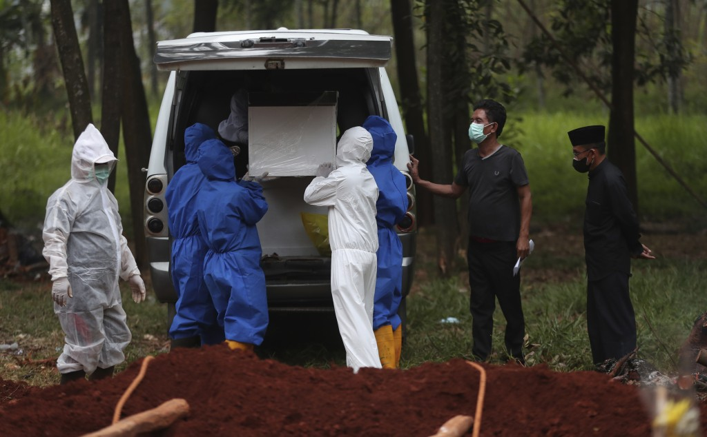 Workers in protective suits remove a coffin containing the body of a COVID-19 victim from an ambulance for burial at Cipenjo cemetery in Bogor, West J...