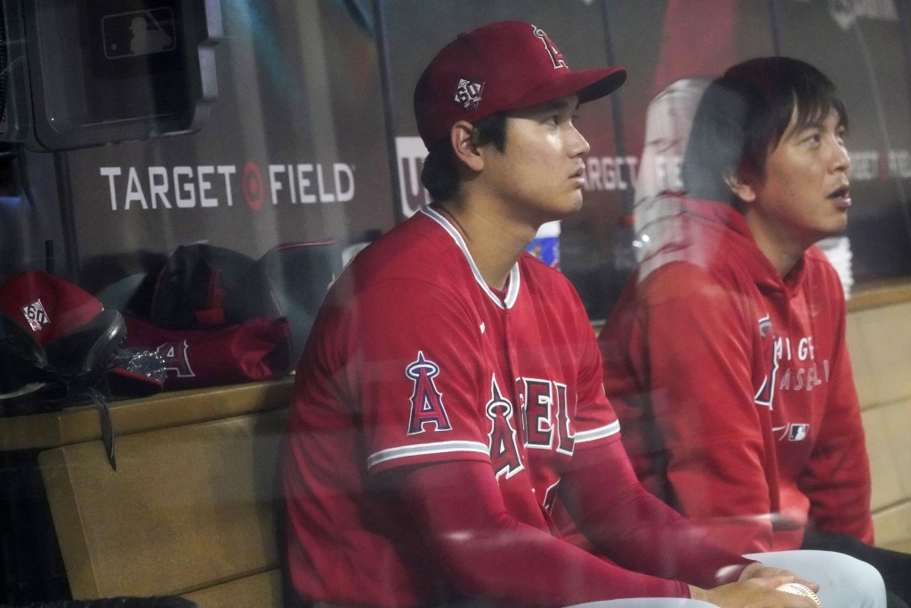 Los Angeles Angels' Shohei Ohtani, left, and his interpreter watch the sixth inning from the dugout as Ohtani did not play against the Minnesota Twins...