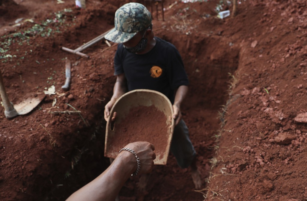 Relatives prepare a grave for a COVID-19 victim at Cipenjo cemetery in Bogor, West Java, Indonesia, on July 14, 2021. With the numbers of death increa...