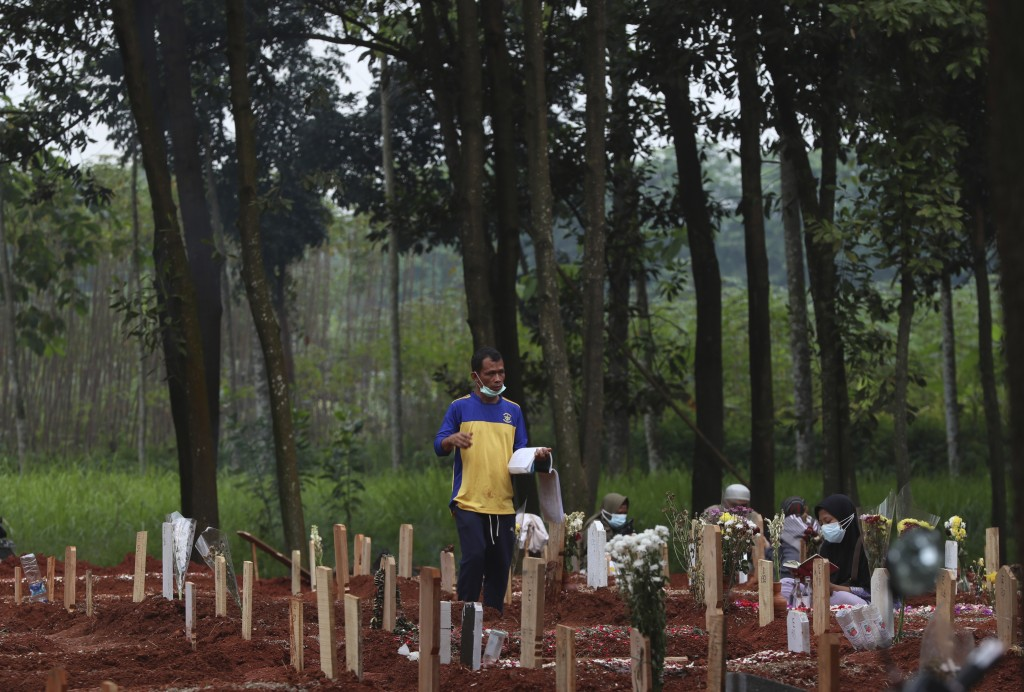 Jaidi, a cemetery worker, walks among graves of COVID-19 victims at Cipenjo cemetery in Bogor, West Java, Indonesia on July 14, 2021. With the numbers...
