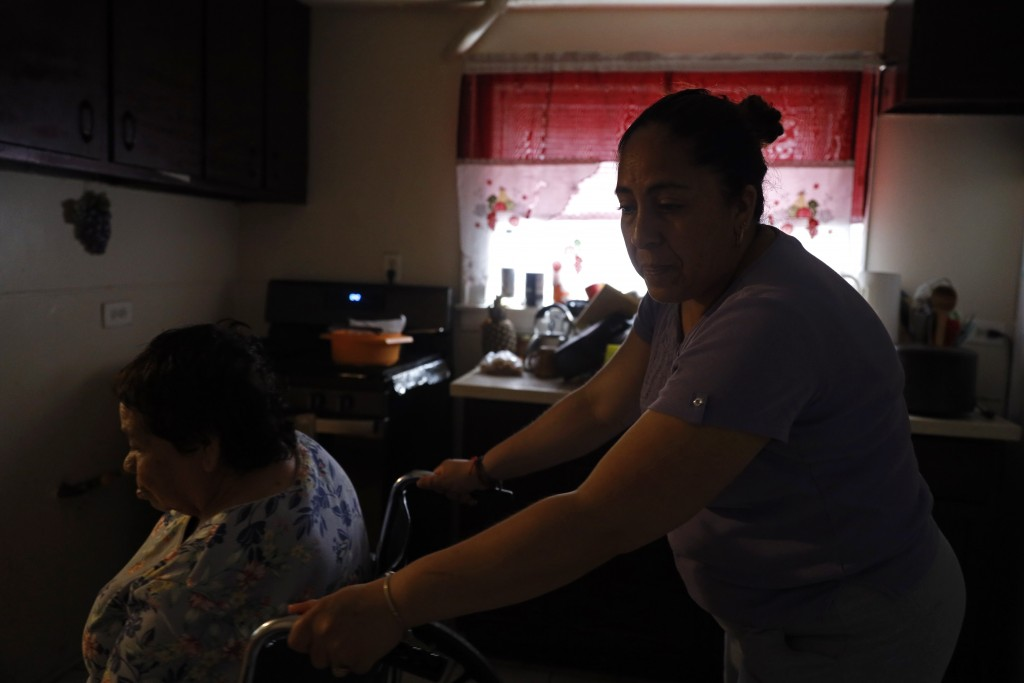 Eugenia Rodriguez, right, maneuvers the wheelchair with her 84-year-old mother, Francisca Perez, who suffers from a heart condition, rheumatoid arthri...