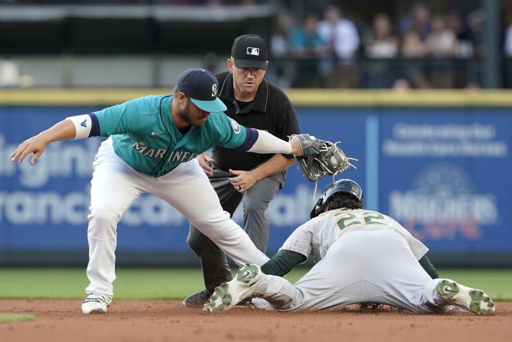 Oakland Athletics' Ramon Laureano, right, is caught stealing second base by Seattle Mariners second baseman Ty France, as umpire Mike Muchlinski watch...