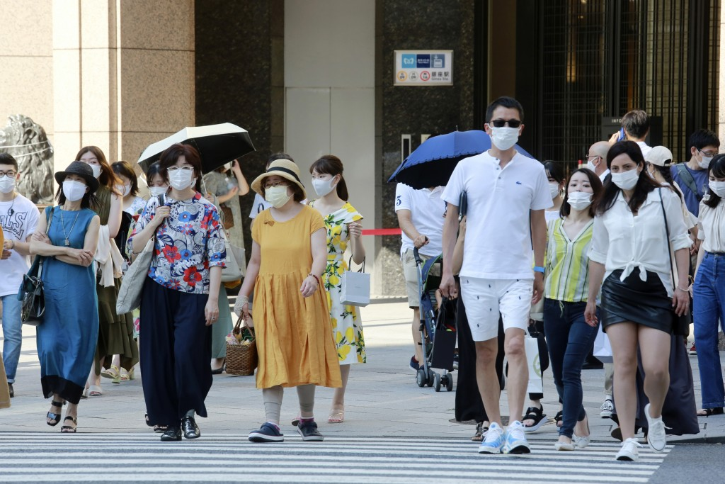 People wearing face masks to protect against the spread of the coronavirus walk on a street in Tokyo Saturday, July 24, 2021. (AP Photo/Koji Sasahara)...