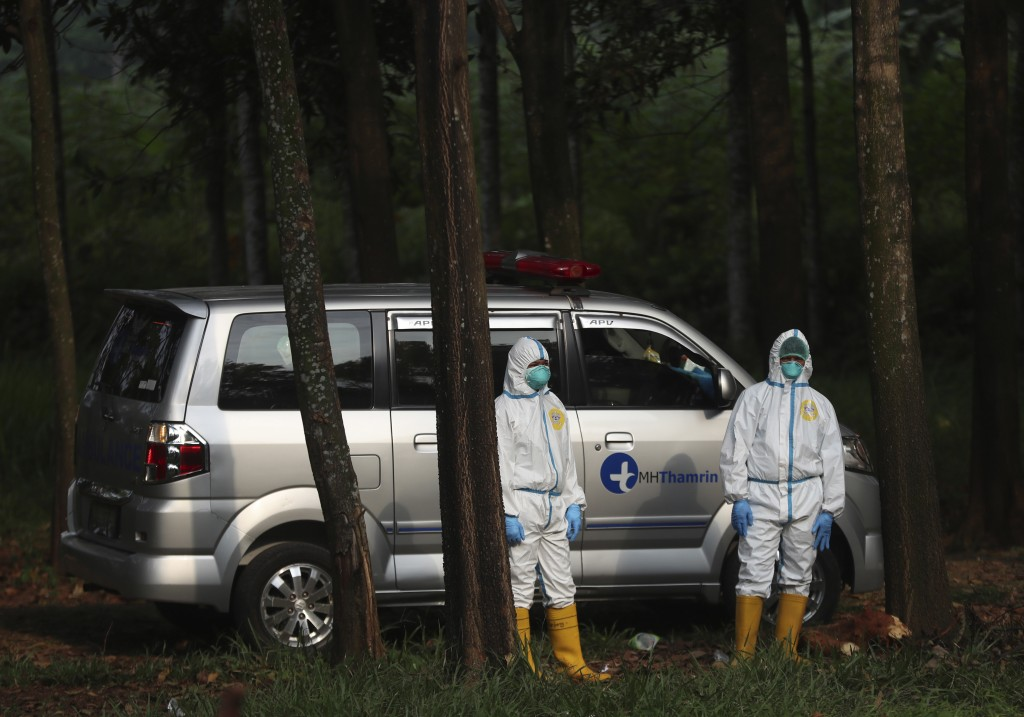 Workers in protective suits stand near an ambulance carrying the body of a COVID-19 victim as they wait for a grave to be prepared, at Cipenjo cemeter...