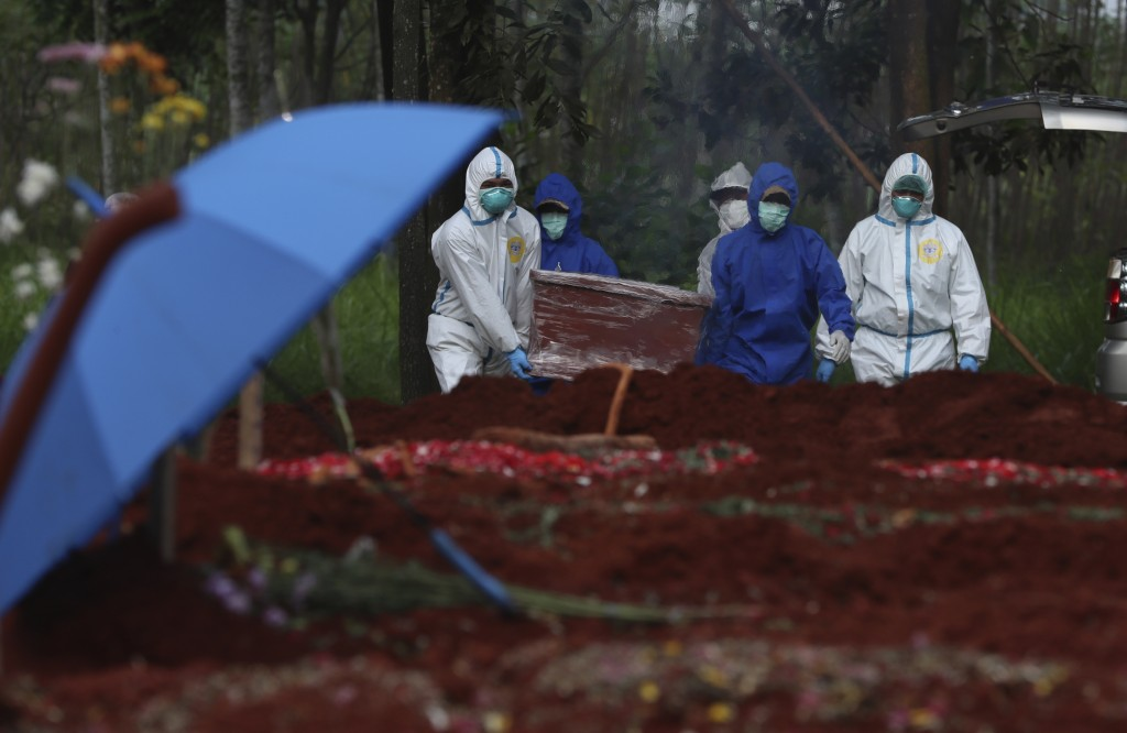 Workers in protective suits carry a coffin containing the body of a COVID-19 victim to a grave for burial at Cipenjo cemetery in Bogor, West Java, Ind...