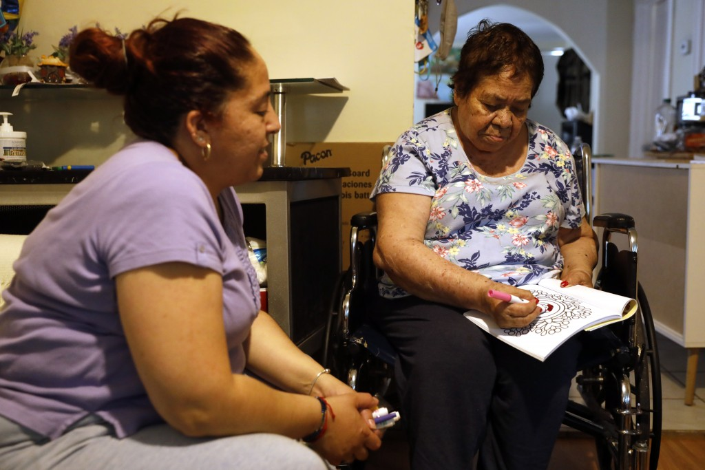 Eugenia Rodriguez, left, looks toward her 84-year-old, non-citizen mother, Francisca Perez, who colors a book, a part of her regular exercise to recov...