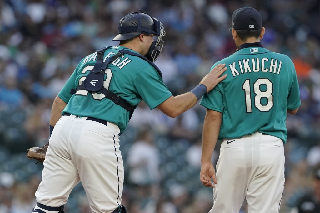 Seattle Mariners catcher Cal Raleigh, left, talks with starting pitcher Yusei Kikuchi during the fourth inning of the team's baseball game against the...