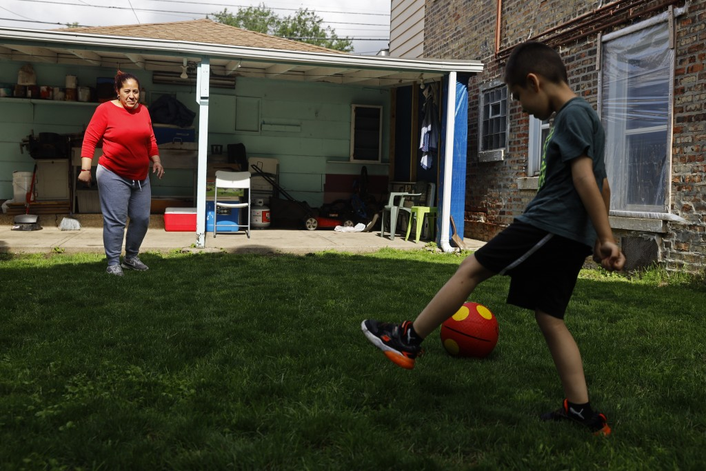 Eugenia Rodriguez, left, plays ball with her youngest son, Aaron, 6, in the backyard of her house Friday, July 2, 2021, in Chicago's Little Village ne...
