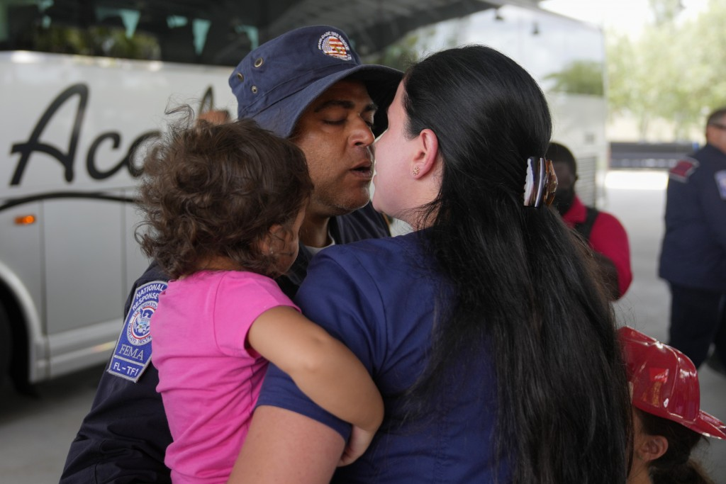 A rescue worker greets his loved ones as members of Miami-Dade Fire Rescue's urban search and rescue team are reunited with their families after weeks...