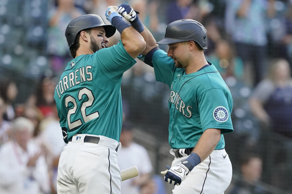 Seattle Mariners' Cal Raleigh, right, is greed by Luis Torrens (22) after Raleigh hit a two-run home run against the Oakland Athletics during the seco...