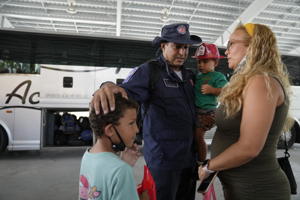 Enrique Calvo greets his sons Alec, 6, Enrique, 2, and wife Joceline, as members of Miami-Dade Fire Rescue's urban search and rescue team are reunited...