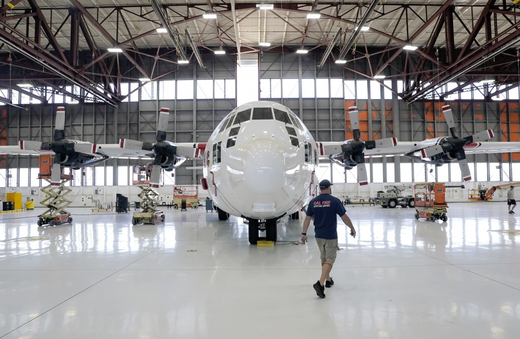 Aircraft Mechanic Cody Poole walks past one of the recently acquired C-130 aircraft, that will be used for firefighting, hangared at the California De...