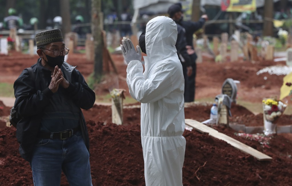 A man gestures as he speaks to a family in protective suit after a burial of a relative at Cipenjo cemetery in Bogor, West Java, Indonesia on July 14,...