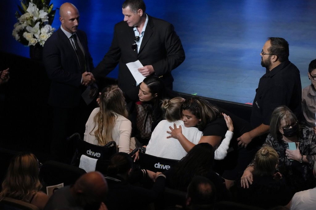 Angela Gonzalez, center, and daughter Deven, left, both seated in wheelchairs due to their injuries, are embraced by well-wishers ahead of the funeral...