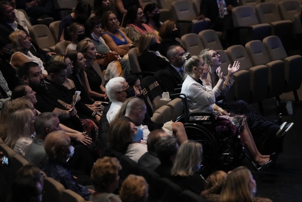 Angela Gonzalez, second from right, and daughter Deven, right, attend in wheelchairs due to their injuries, during the funeral service for their late ...