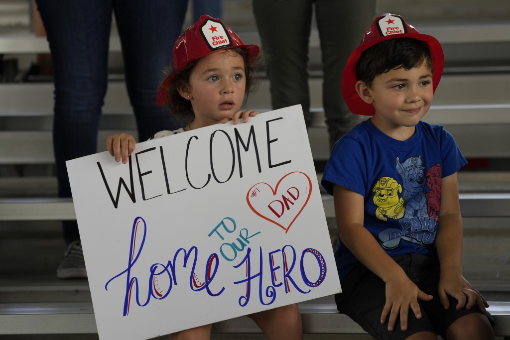 Isabella, 3, and Eric, 4, wait to welcome home their father, Capt. Eric Hernandez, as members of Miami-Dade Fire Rescue's urban search and rescue team...