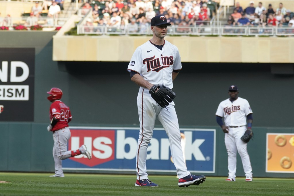 Minnesota Twins pitcher J.A. Happ, center, waits as Los Angeles Angels' Kurt Suzuki, left, rounds the bases on a two-run home run during the first inn...