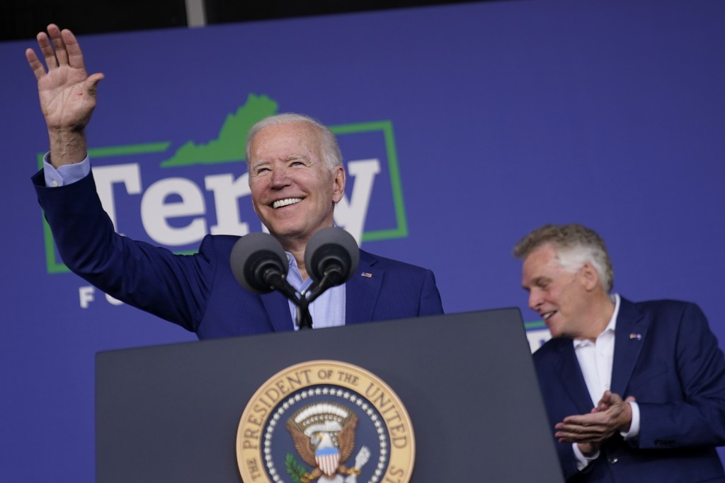 President Joe Biden waves as he arrives to speak at a campaign event for Virginia democratic gubernatorial candidate Terry McAuliffe, right, at Lubber...