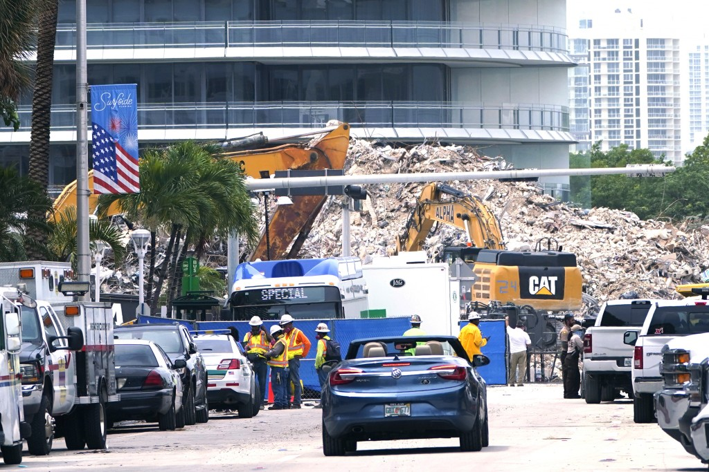 FILE - In this July 13, 2021 file photo, crews work in the rubble of the Champlain Towers South building, as removal and recovery work continues at th...
