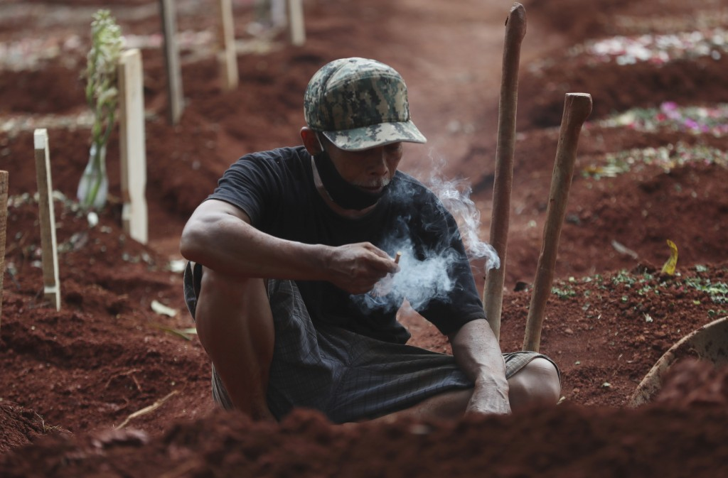 A man takes a break after preparing a grave for a relative who died of COVID-19, at Cipenjo cemetery in Bogor, West Java, Indonesia on July 14, 2021. ...