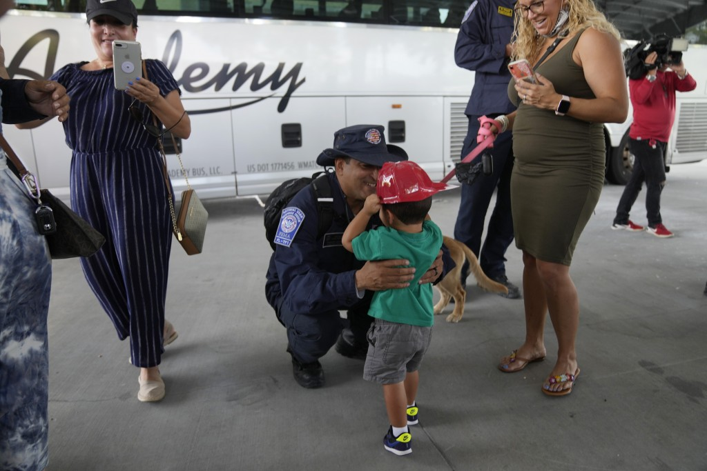 Enrique Calvo greets his son Enrique, 2, as his wife Joceline looks on, as members of Miami-Dade Fire Rescue's urban search and rescue team are reunit...