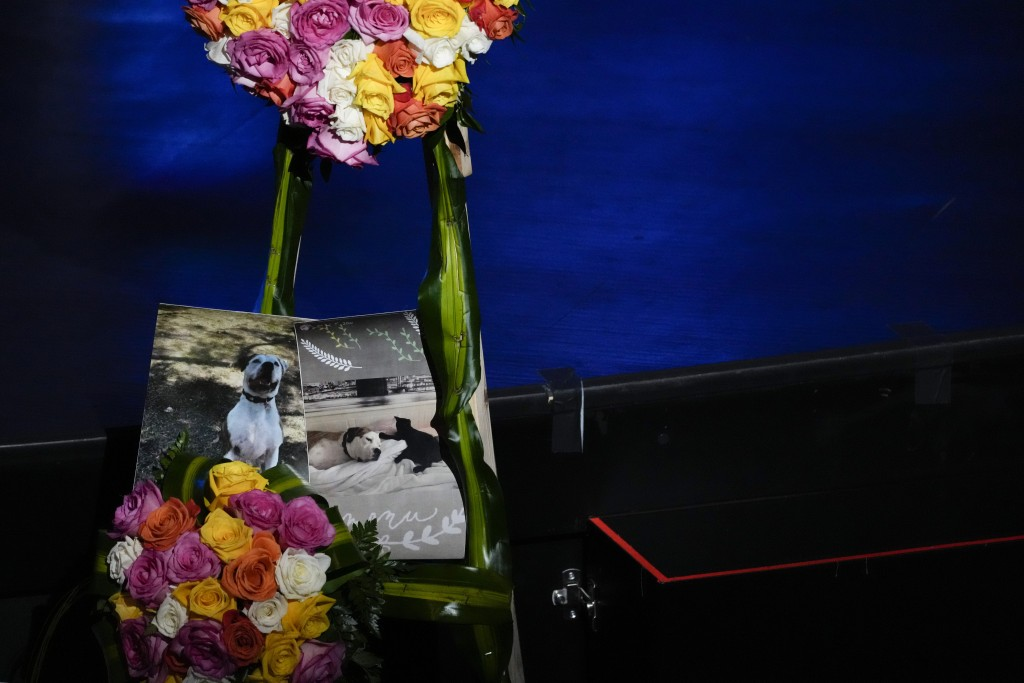 Pictures of Gonzalez family pets also lost in the disaster are displayed next to flowers at the funeral of Edgar Gonzalez, 44, who was killed last mon...