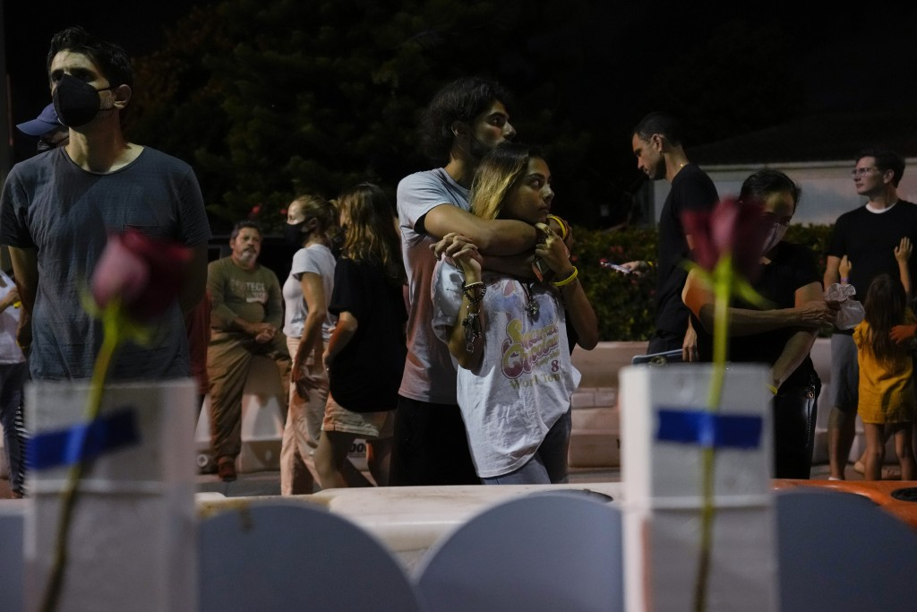 FILE - In this July 15, 2021 file photo, well-wishers and mourners gather at a makeshift memorial for the victims of the Champlain Towers South condo ...