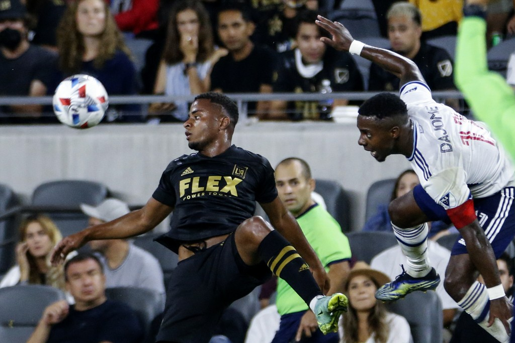 Vancouver Whitecaps midfielder Cristian Dajome, right, and Los Angeles FC defender Diego Palacios watch the ball during the second half of an MLS socc...