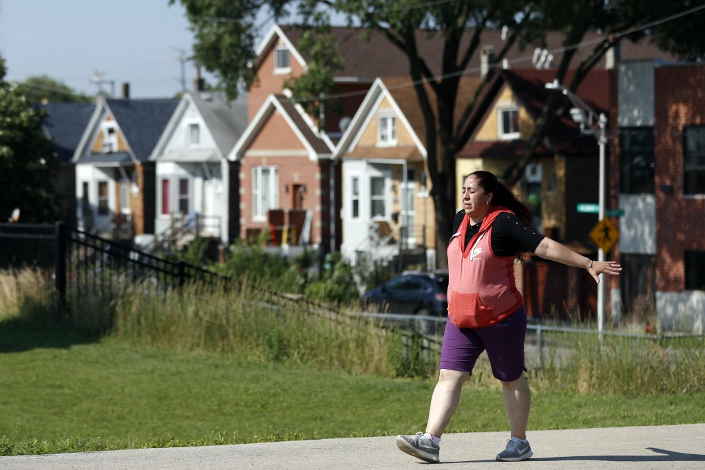 Eugenia Rodriguez walks in Chicago's La Villita Park, Thursday, July 1, 2021. She is required to get out for a walk or a run every morning to keep her...