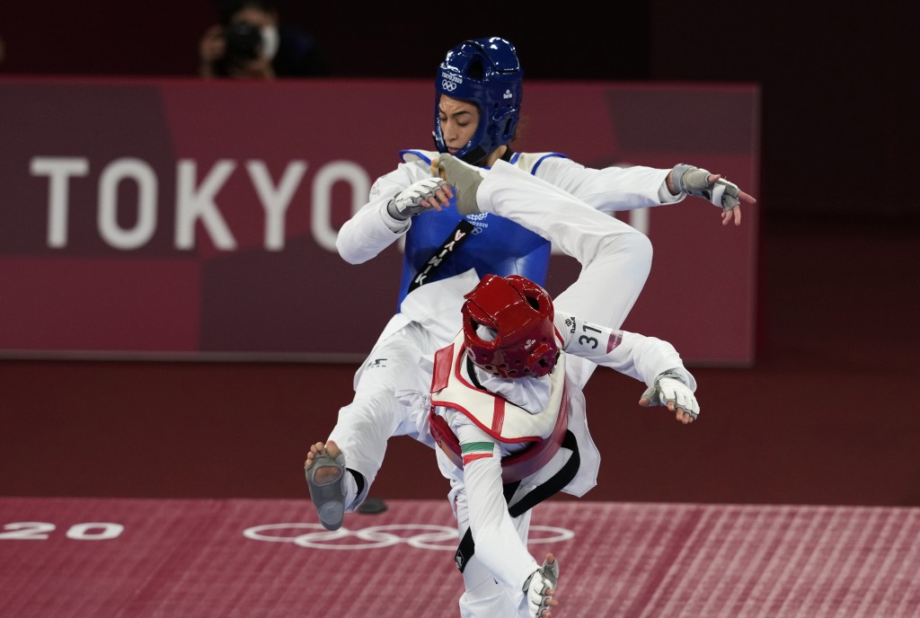 Iran's Nahid Kiyani, front, attacks Kimia Alizadeh Zonoozi, of the Refugee Olympic Team, during the women's 57kg match at the 2020 Summer Olympics, Su...