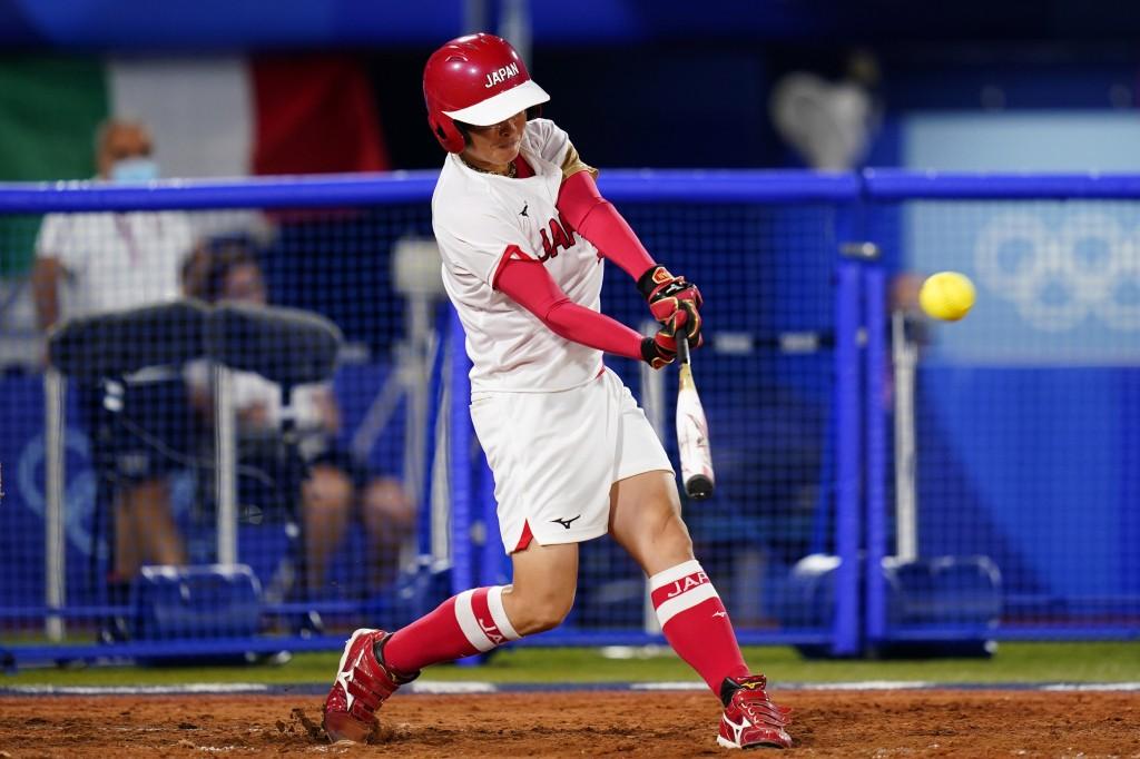 Japan's Yamato Fujita hits a three-run home run during a softball game against Italy at Yokohama Baseball Stadium during the 2020 Summer Olympics, Sat...