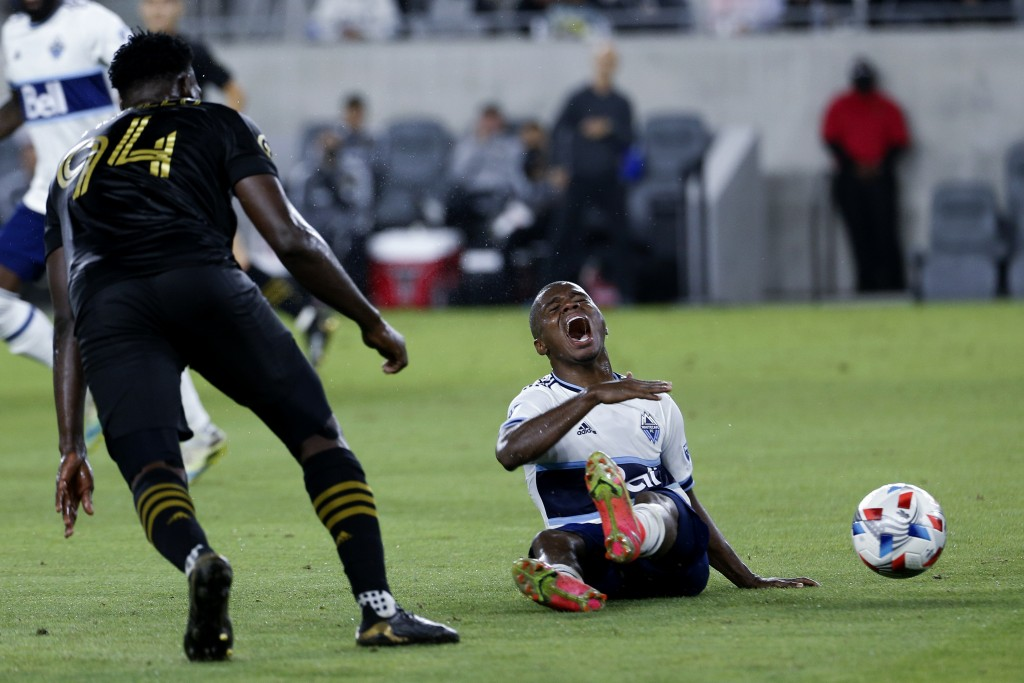 Vancouver Whitecaps midfielder Deiber Caicedo, right, reacts after a foul by Los Angeles FC defender Jesus David Murillo (94) during the second half o...