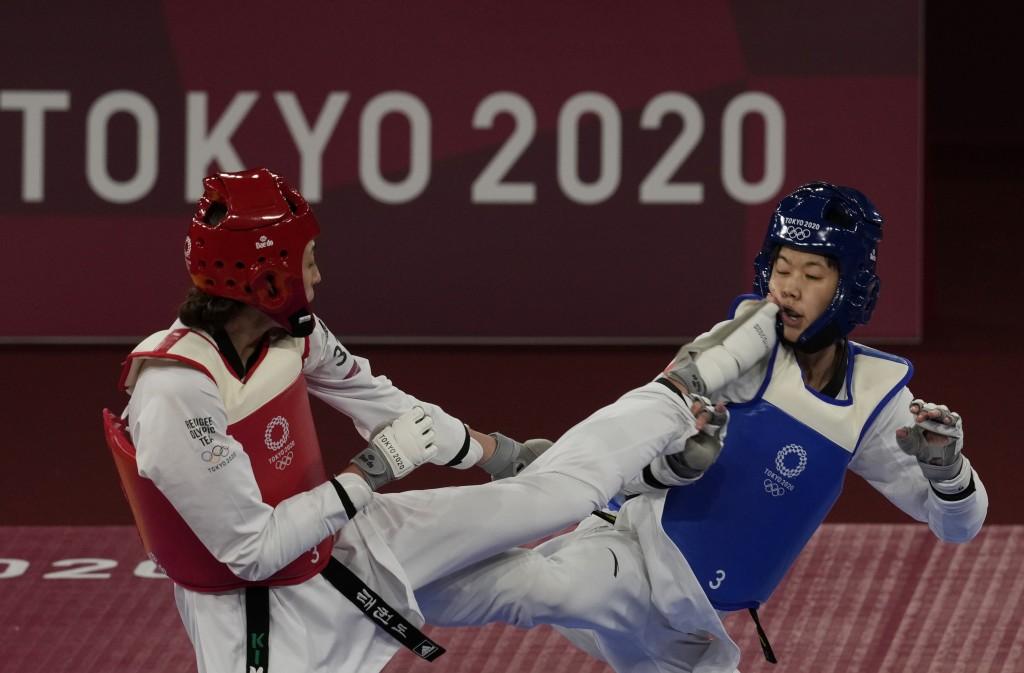 Kimia Alizadeh Zonoozi, Refugee Olympic Team, left, attacks China's Zhou Lijun during the taekwondo women's 57kg match at the 2020 Summer Olympics, Su...