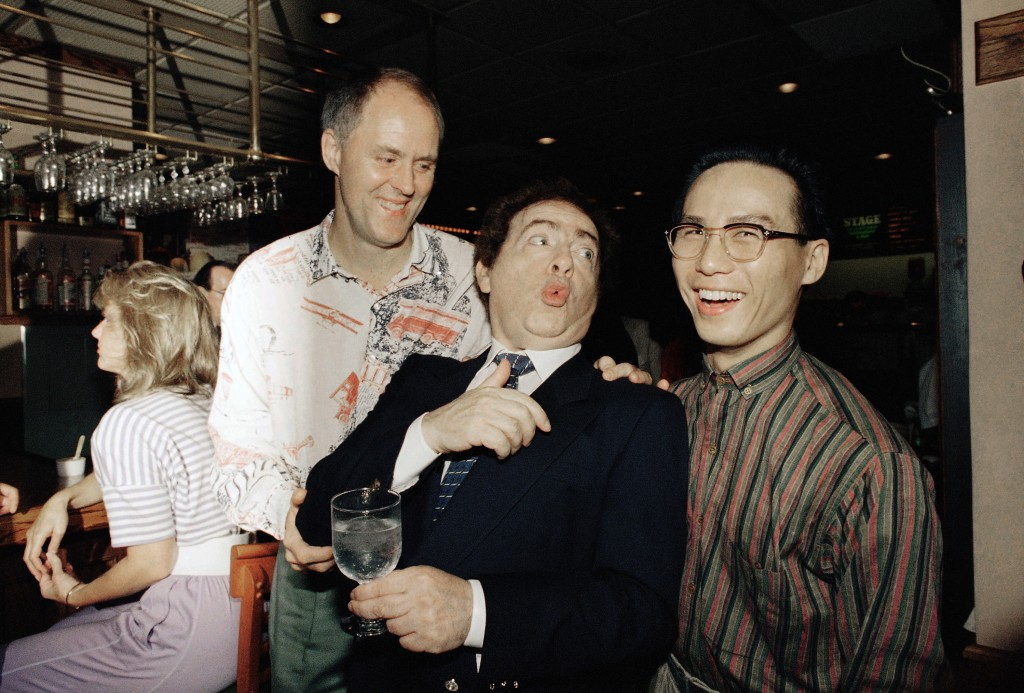 FILE - In this  July 21, 1988, file photo, comedian Jackie Mason, holding a glass, enjoys a joke with John Lithgow, left, and B.D. Wong, stars of the ...