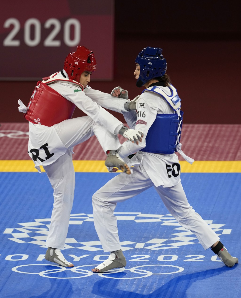 Iran's Nahid Kiyani, left, attacks Kimia Alizadeh Zonoozi, of the Refugee Olympic Team, during the women's 57kg match at the 2020 Summer Olympics, Sun...