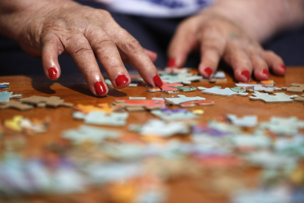 Francisca Perez, 84, rearranges puzzle pieces, a part of her regular exercise to recover from rheumatoid arthritis, Wednesday, June 30, 2021, in Chica...