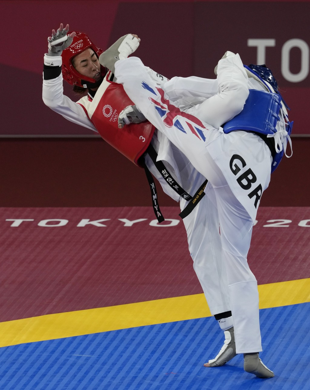 Kimia Alizadeh Zonoozi, Refugee Olympic Team, is attacked by Britain's Jade Jones during the taekwondo women's 57kg match at the 2020 Summer Olympics,...