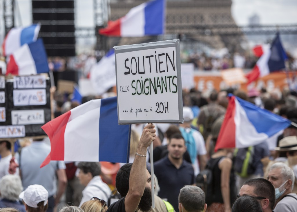 """A banner that reads: """"Support to health workers and not only at 8pm"""", is held up during a demonstration in Paris, France, Saturday 24, 2021, against t..."""