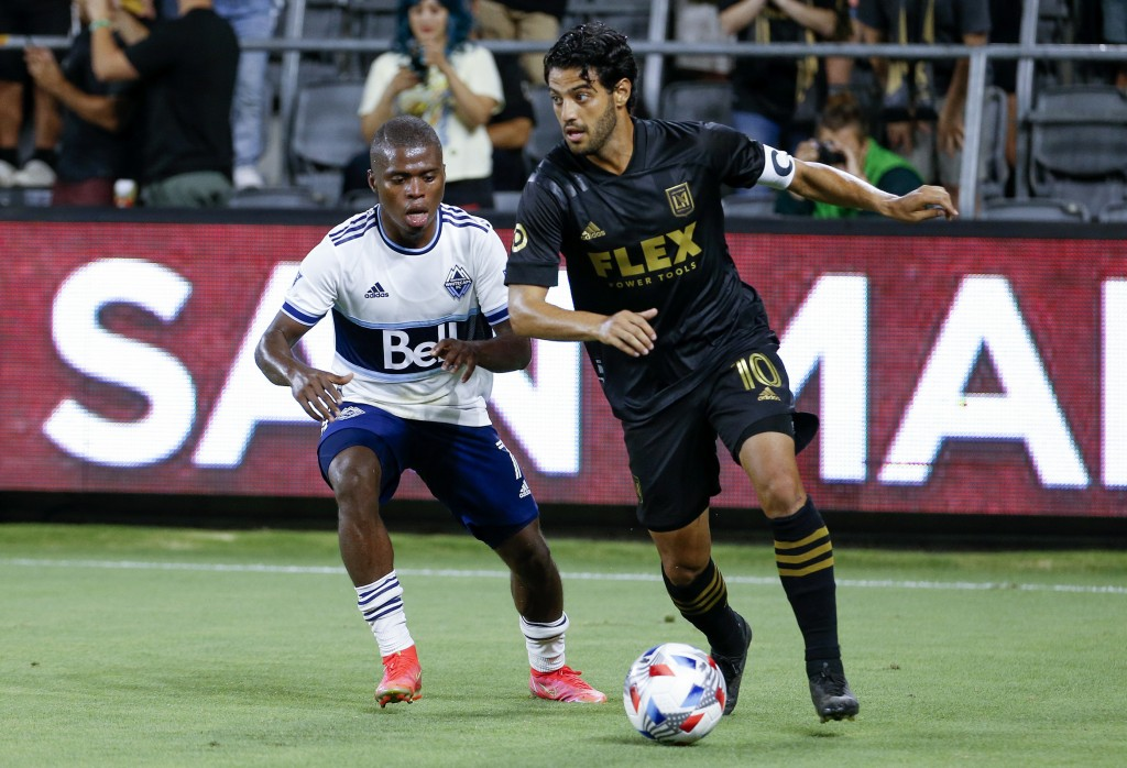 Los Angeles FC forward Carlos Vela (10) drives the ball past Vancouver Whitecaps midfielder Deiber Caicedo (7) during the second half of an MLS soccer...