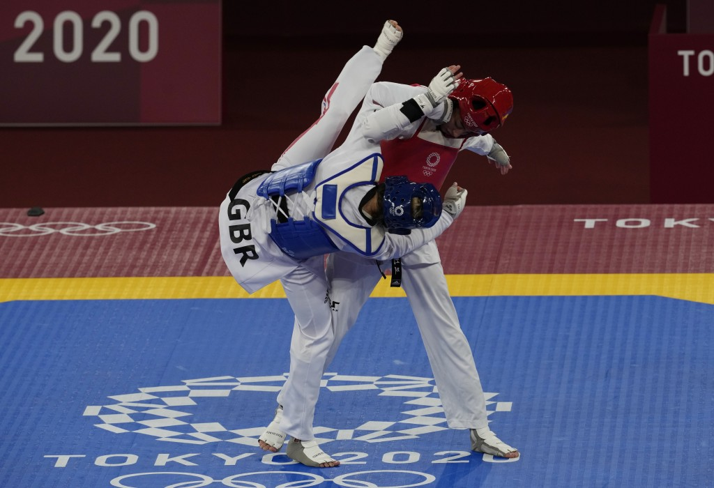 Kimia Alizadeh Zonoozi, Refugee Olympic Team, right, is attacked by Britain's Jade Jones during the taekwondo women's 57kg match at the 2020 Summer Ol...