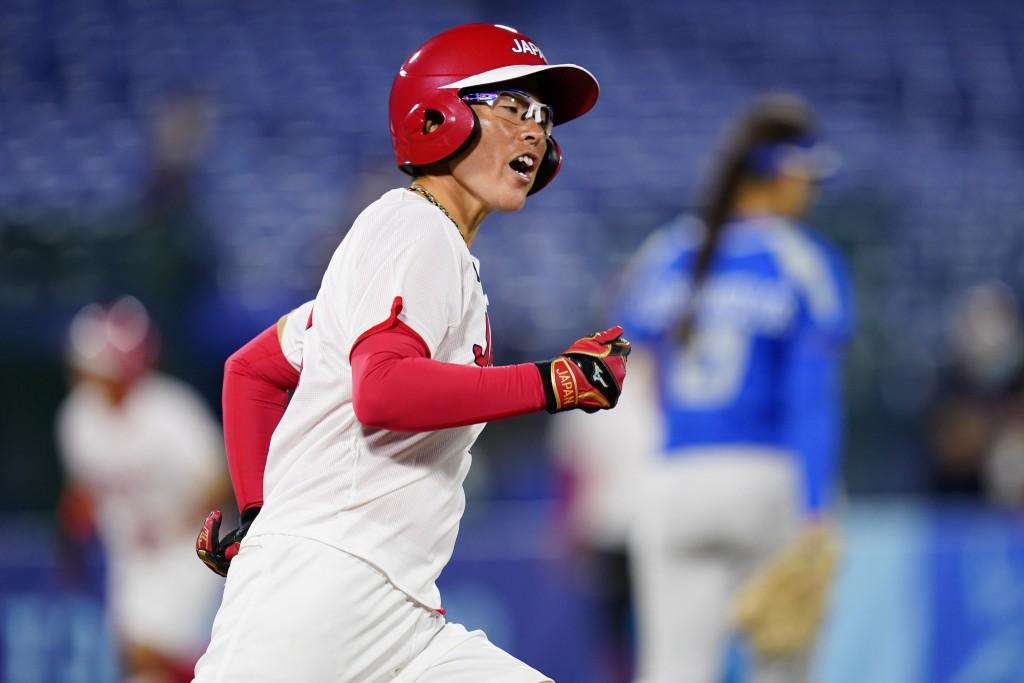 Japan's Yamato Fujita reacts after hitting a three-run home run during a softball game against Italy at Yokohama Baseball Stadium during the 2020 Summ...