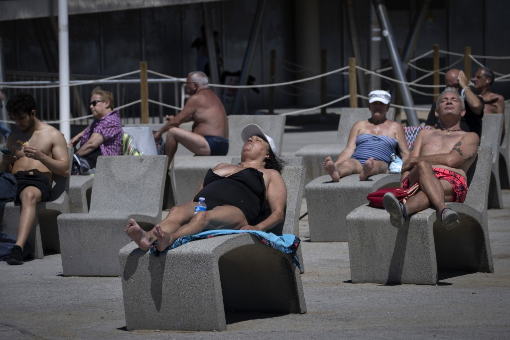 FILE - In this Tuesday, June 8, 2021 file photo, people sunbathe near the beach in Barcelona, Spain. For Europe's battered tourism industry, chaos and...