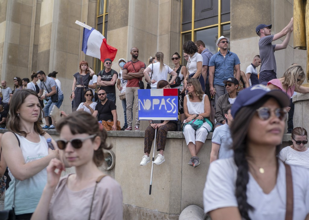 People attend a demonstration in Paris, France, Saturday 24, 2021, against the COVID-19 pass which grants vaccinated individuals greater ease of acces...