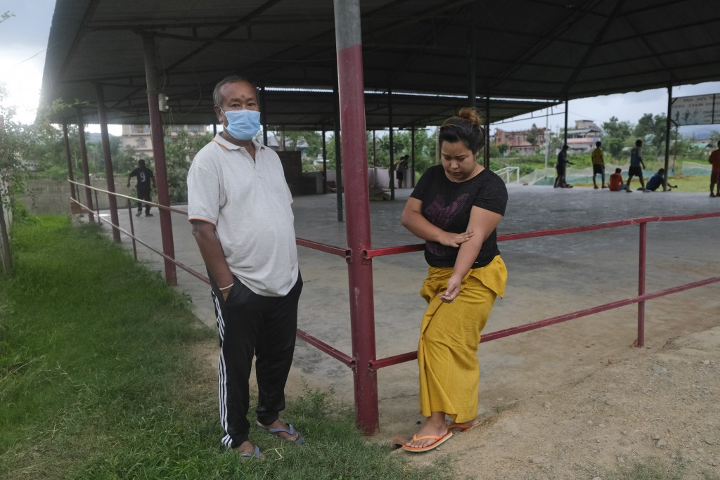 Diana Khumanthem, 30, stands beside her father Yaima Khumanthem, 75, in a public gathering space where Yaima chooses to spend his day after his wife a...
