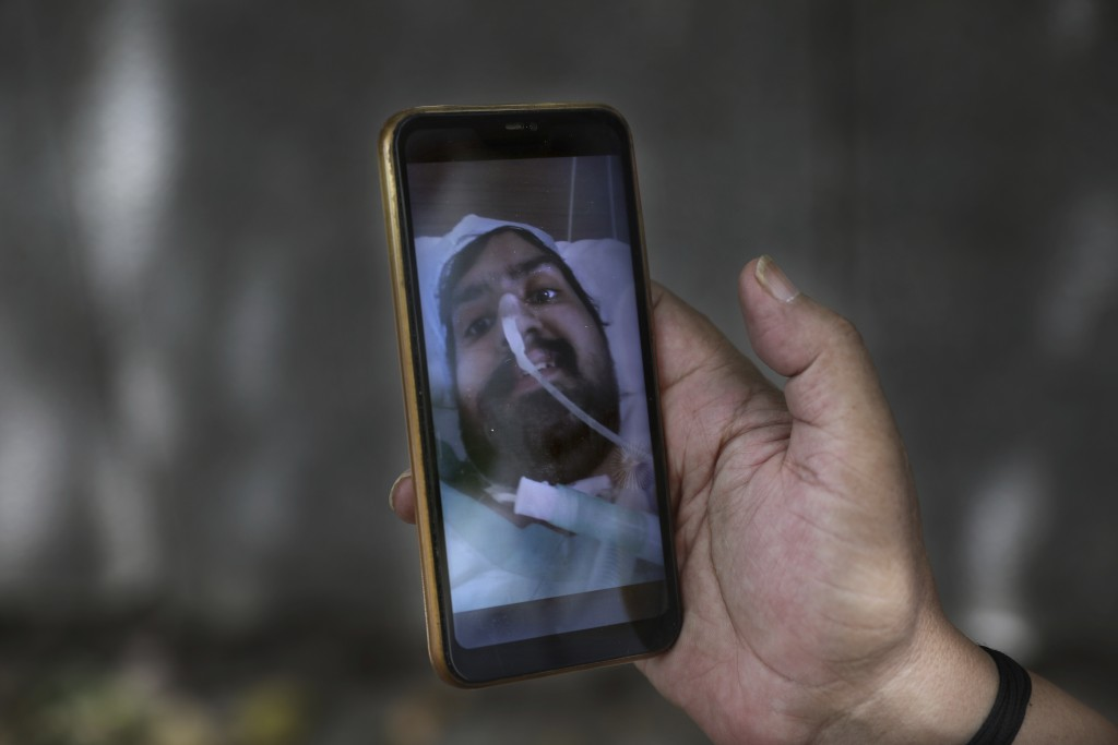 Anil Sharma shows a photograph of his son Saurav who is being treated for COVID-19 at a private hospital in New Delhi, India, Thursday, July 1, 2021. ...
