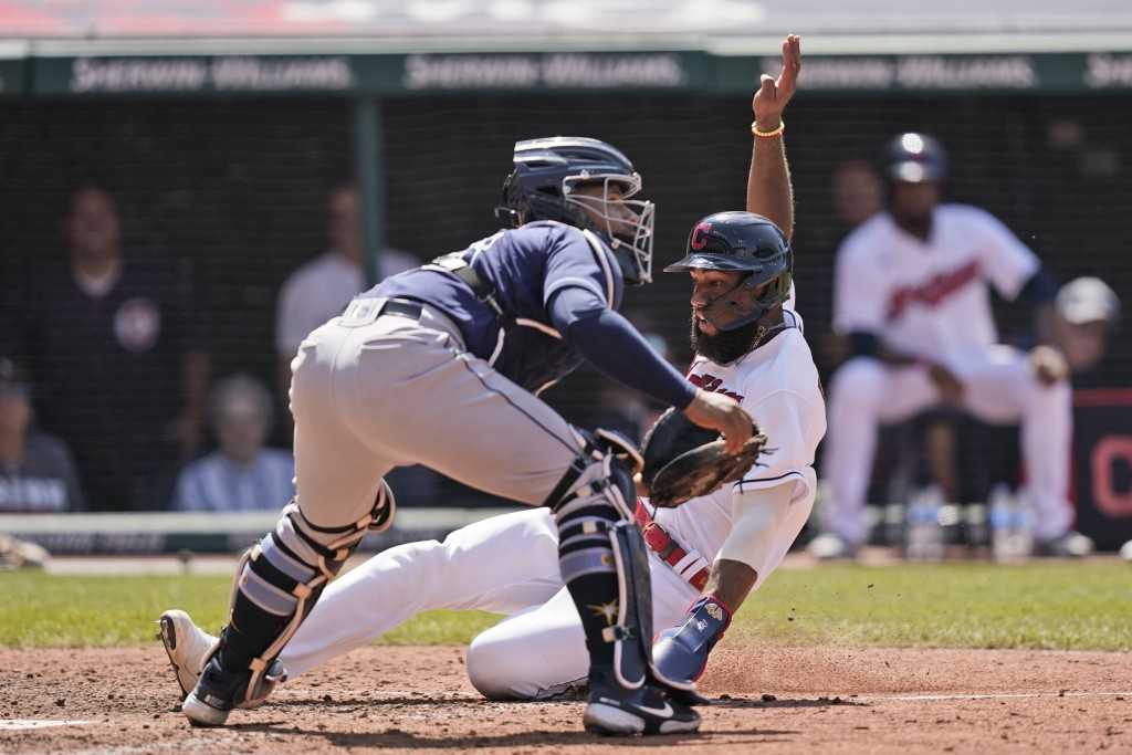 Cleveland Indians' Amed Rosario, right, scores as Tampa Bay Rays catcher Francisco Mejia waits for the ball in the eighth inning of a baseball game, S...