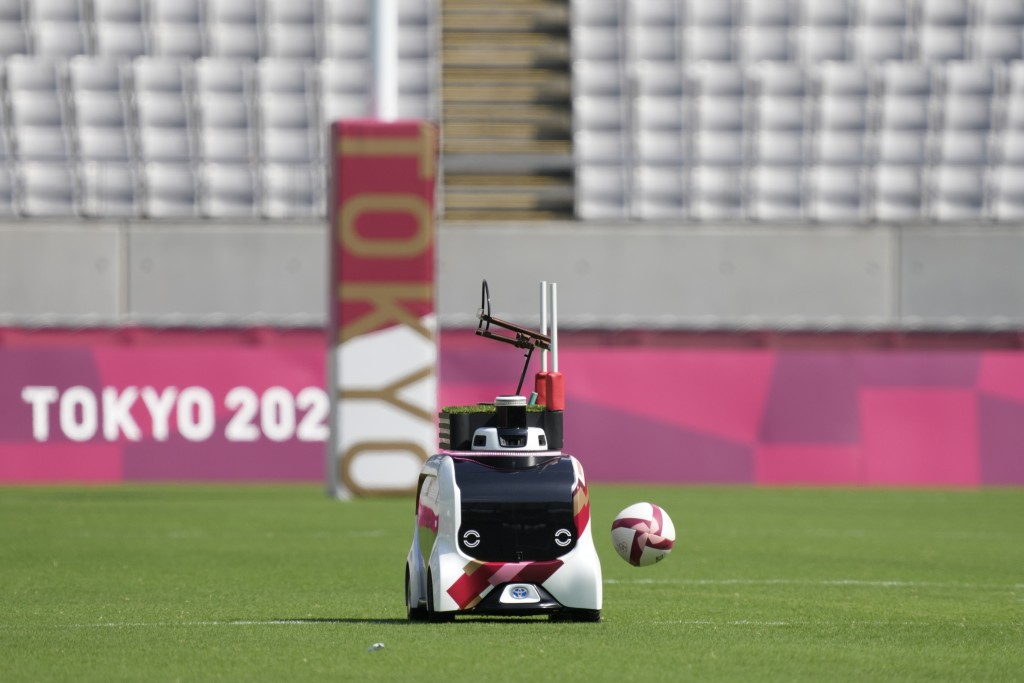 A ball carrier vehicle passes by empty stands before the start of the men's rugby sevens match at the 2020 Summer Olympics, Monday, July 26, 2021, in ...