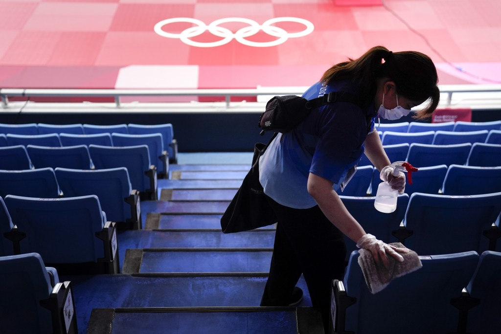 FILE - In this July 24, 2021, file photo, worker disinfects the seats before judo matches at the 2020 Summer Olympics in Tokyo, Japan. (AP Photo/Jae C...